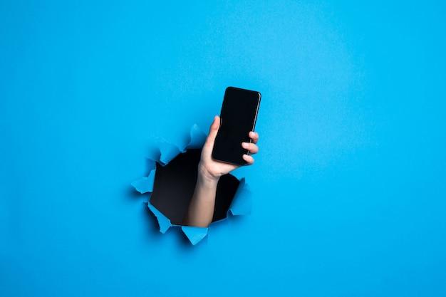 종이 벽에 파란색 구멍을 통해 전진에 대 한 Screan와 전화를 들고 여자 손의 닫습니다. 무료 사진