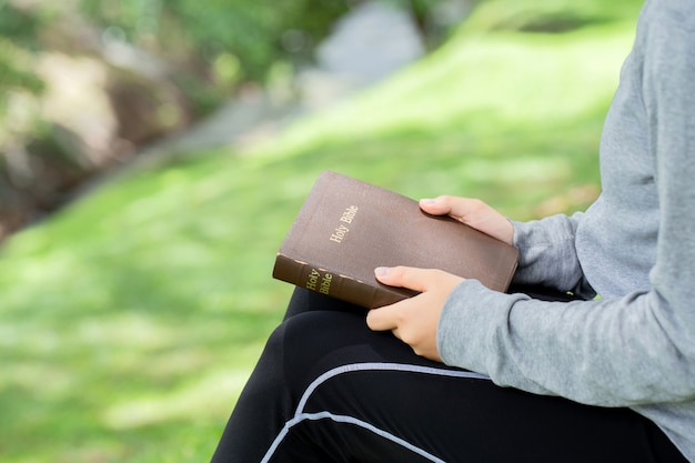 緑の背景にボケ味の光、コピー領域の聖書を保持している女性の手のクローズアップ Premium写真