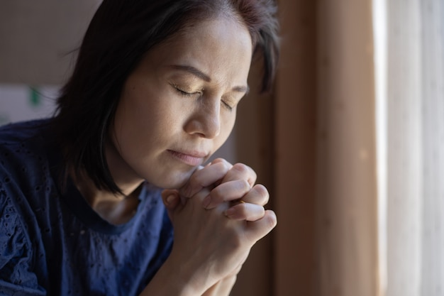 教会で祈る女性の手のクローズアップ。 Premium写真