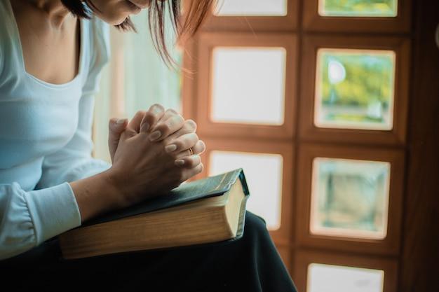 教会で祈っている女性の手のクローズアップ、女性は神を信じて祈っています。 Premium写真
