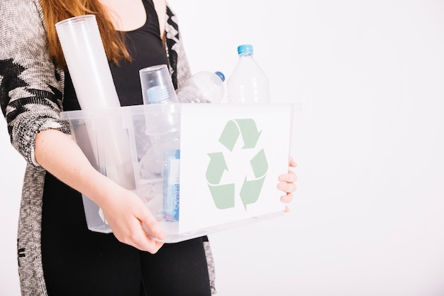 Close-up of woman holding crate full of plastic items for recycling Free Photo
