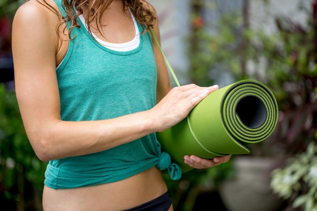 Close-up of woman holding yoga mat outdoors Free Photo