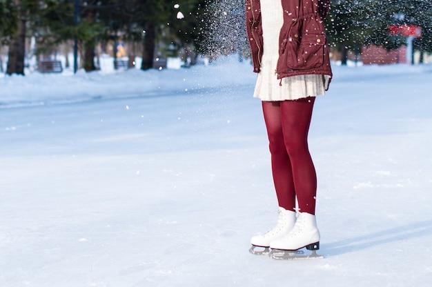 オープンスケートリンクで白い革のスケート靴を履いている女性の足のクローズアップ。テキストの場所 Premium写真
