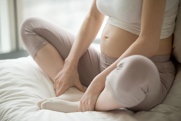 Close-up of woman placing her feet to meditate Free Photo