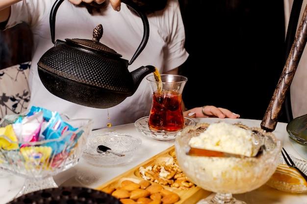 Крупным планом женщина наливает черный чай из черного чугуна чайник Бесплатные Фотографии