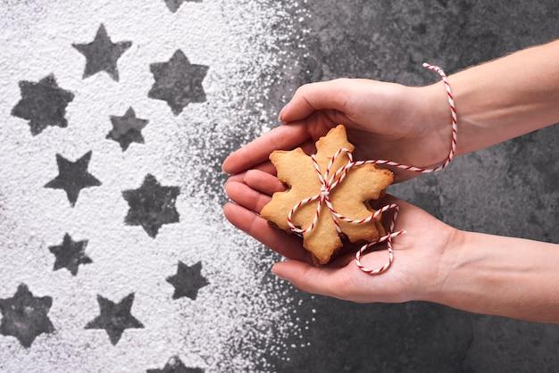 ジンジャーブレッドクッキーを保持している女性の手のクローズアップ 無料写真