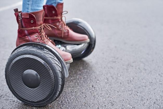 Закройте вверх женщины используя дорогу hoverboard onsphalt, ноги на электрическом самокате напольном Premium Фотографии