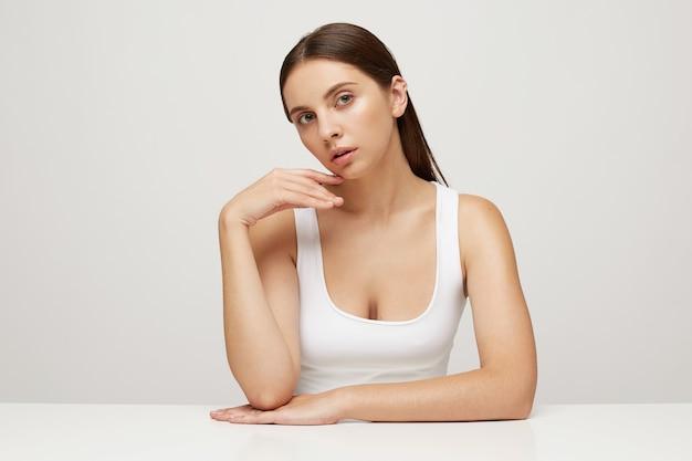 テーブルに座っている完璧な健康的な新鮮な肌を持つ女性のクローズアップ 無料写真