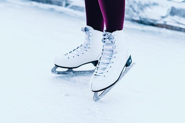 オープンスケートリンクで冬のスケートの女性の足のクローズアップ。 Premium写真