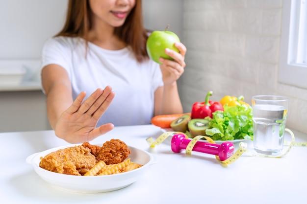 Закройте молодой азиатской женщины с помощью руки вытолкнуть нездоровую пищу и выбрать здоровую пищу. Premium Фотографии