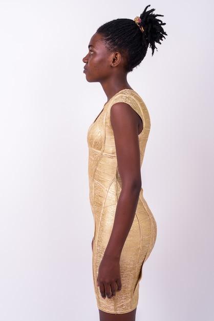 孤立したパーティーの準備ができて金のドレスを着て若い美しいアフリカの女性のクローズアップ Premium写真
