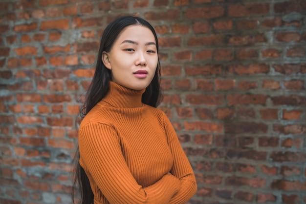 Закройте вверх молодой красивой азиатской женщины смотря уверенно и стоящей против кирпичной стены. Premium Фотографии