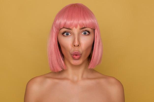 Крупный план молодой красивой розоволосой девушки с короткой модной стрижкой, округляющей ее голубые глаза, удивленно смотрящей в камеру, надутой губой и позирующей на горчичном фоне Бесплатные Фотографии