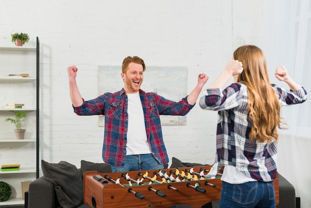 Крупный план молодая пара празднует победу после игры в настольный футбол Бесплатные Фотографии