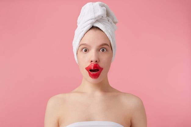 スパの後の若いぼんやりした女性のクローズアップは、彼女の頭にタオルをつけて、大きく開いた目と口で、唇のパッチ、立っています。 無料写真