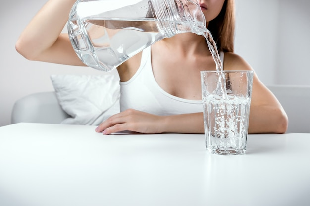 Close up of young girl pouring fresh pure water from pitcher into a glass Premium Photo