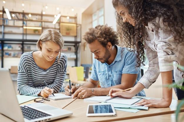 Крупным планом молодой группы стартаперов, сидя в библиотеке, делая исследование о будущем проекте тем, просматривая графики на ноутбуке, писать новые идеи. бизнес, концепция совместной работы Бесплатные Фотографии