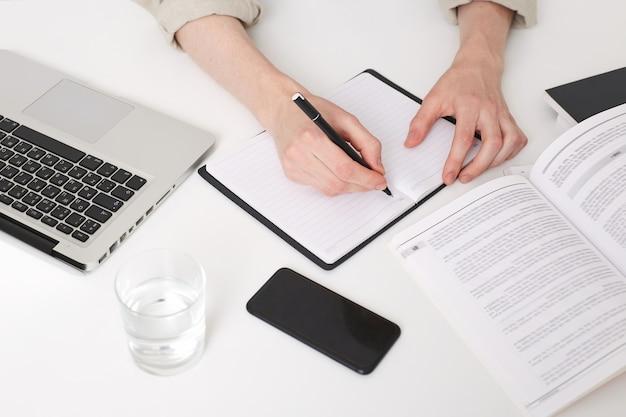 Крупным планом руки молодого человека писать заметки Бесплатные Фотографии