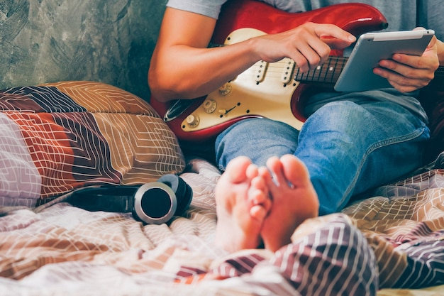 Close Up Of Young Man Using Tablet And Playing Electric Guitar On