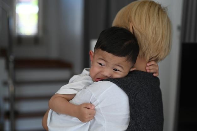家で泣いている赤ん坊の息子を落ち着かせようとしている若い母親のクローズアップ Premium写真