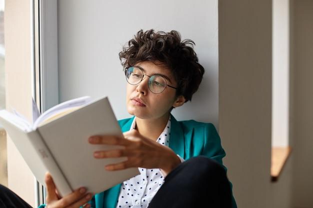 手に本を持って、窓辺に座って、集中した顔で中を見る眼鏡の若いかなり茶色の目の短い髪の巻き毛の女性のクローズアップ 無料写真