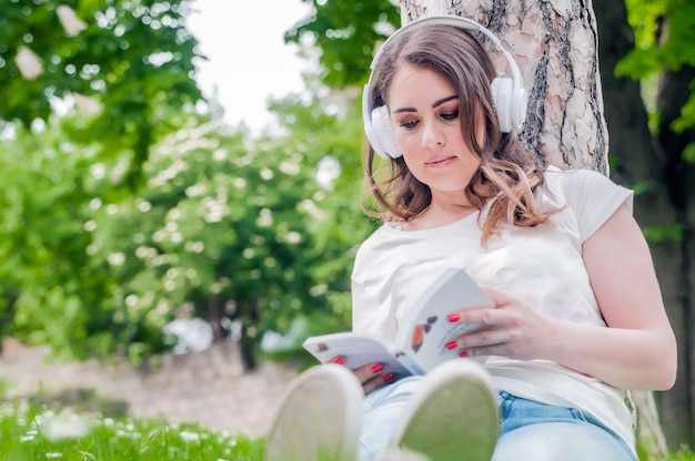 Close-up of young relaxed woman reading and listening music on headphones outside in a spring day. Freetime concept with beautiful female relaxing outdoors with music, books and coffee Free Photo