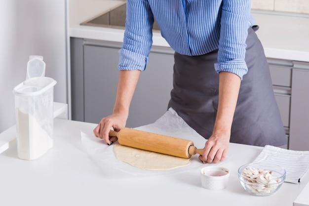 若い女性のクローズアップは、白いテーブルに麺棒で生地を平らに 無料写真