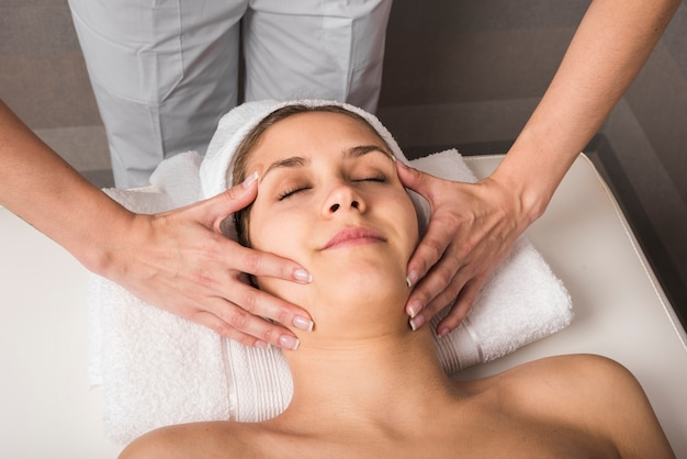 Close-up of young woman getting spa massage treatment at beauty spa salon Free Photo