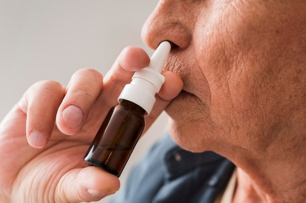 Close-up old man using nasal spray Free Photo