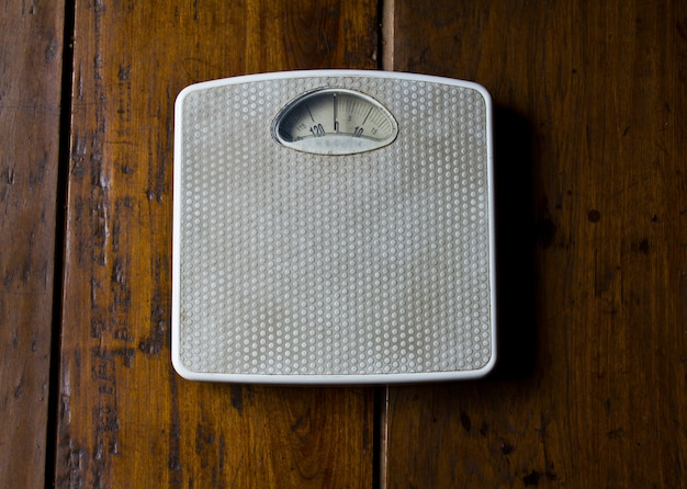 Close up of old scale on wooden floor . Free Photo