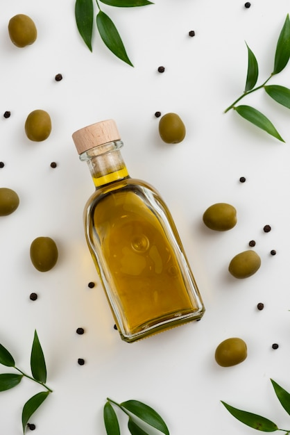 Close-up olive oil bottle with leaves next Free Photo