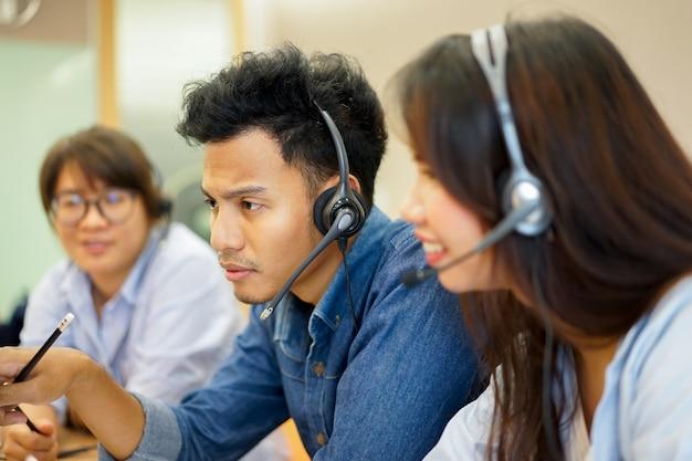 従業員の男性とオフィスコンピュータの作業センターコールホットラインのチームに近づく Premium写真