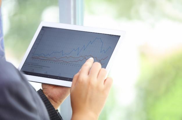 그래프 데이터와 태블릿 화면 디스플레이를 만지고 손에 가까이 프리미엄 사진