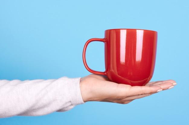 Закройте под рукой с красной кружкой и ручкой Premium Фотографии