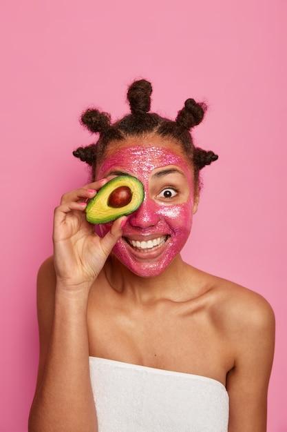 Крупным планом на счастливой этнической женщине нравится применять изолированную маску для лица Бесплатные Фотографии