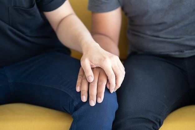 膝の上に手を握ってlgbtゲイカップルのクローズアップ Premium写真