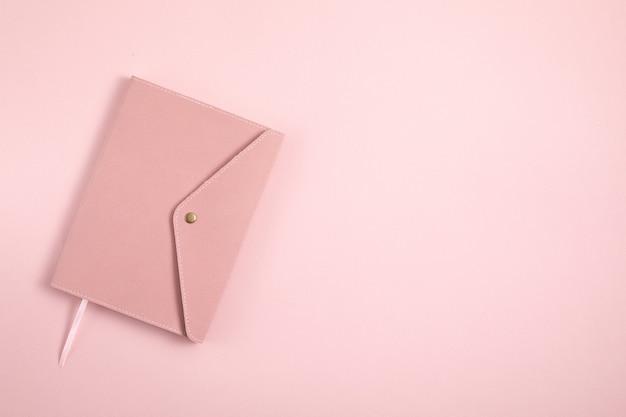 ピンクのノートブックのミニマルなデザインのクローズアップ Premium写真