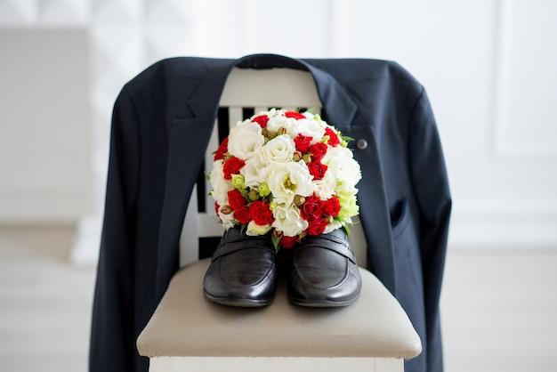 Закройте на туфлях с букетом цветов и куртке на стуле Premium Фотографии