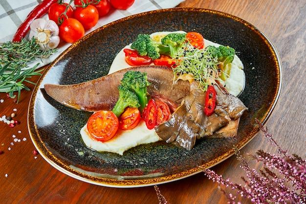 Закройте вверх на вкусном испеченном говяжьем стейке языка с свежими овощами и картофельным пюре в черной плите на деревянном столе. Premium Фотографии