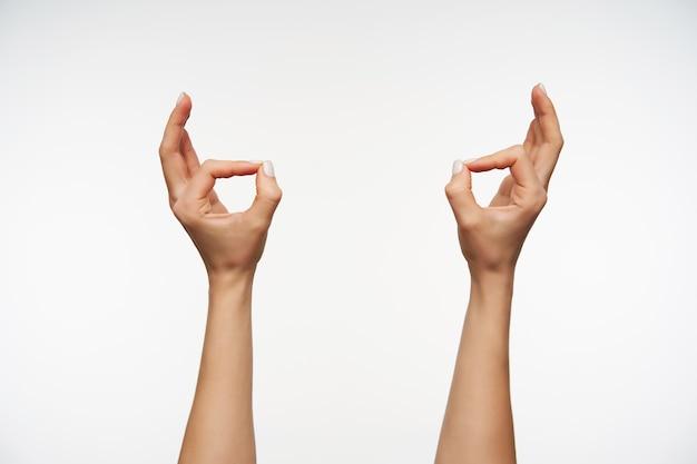 殺人ジェスチャーを形成する白いマニキュアで若い女性の手をクローズアップ 無料写真
