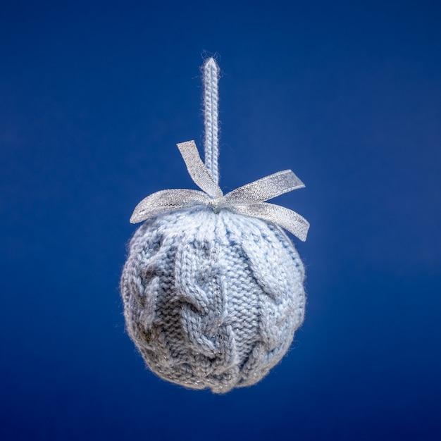 Закройте один висит серый вязаный творческий рождественский шар на ярко-синем квадрате Premium Фотографии