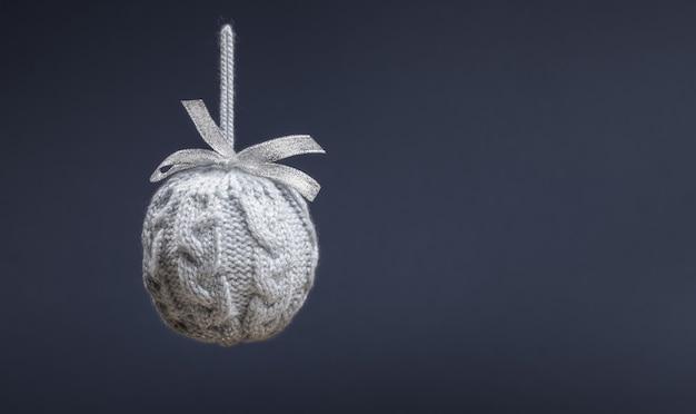 Крупным планом один висит серый вязаный творческий рождественский шар на сером Premium Фотографии