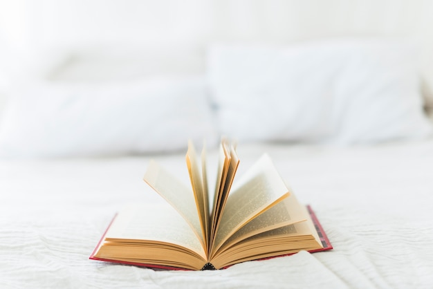 Close-up of open book on bed Free Photo