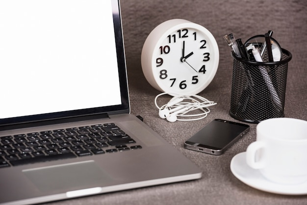 Close-up of an open digital tablet with alarm clock; cell phone and office supplies on desk Free Photo