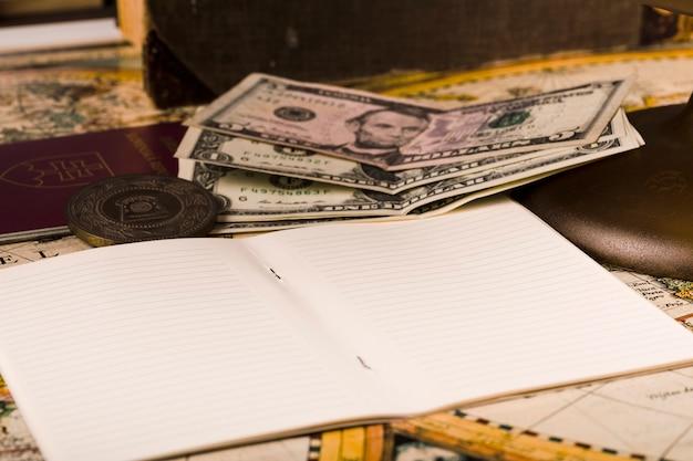 Primo piano del blocco note aperto con banconote e passaporto Foto Gratuite