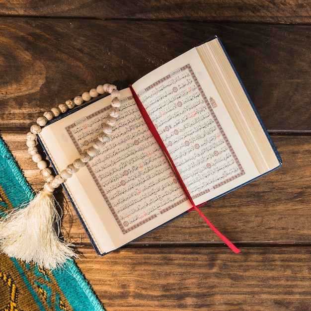 Close-up opened quran and beads near mat Free Photo