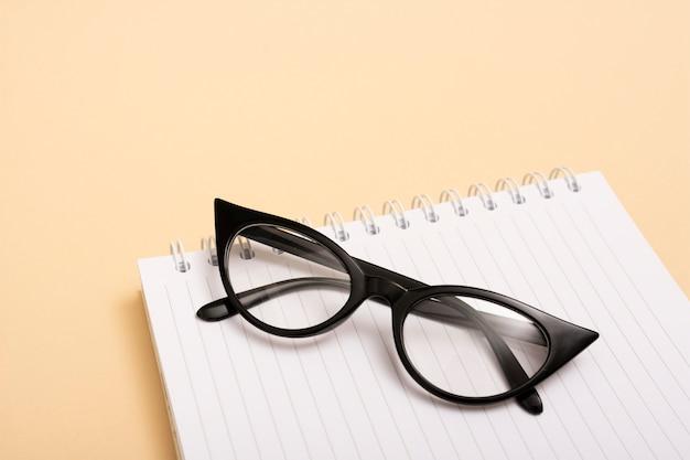 Occhiali ottici del primo piano su un taccuino Foto Gratuite