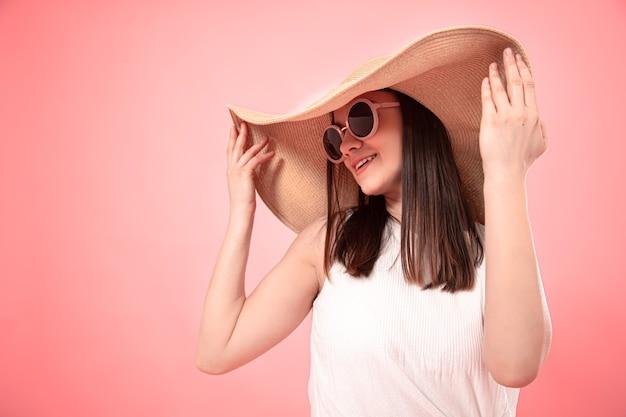 Закройте вверх по ortrait молодой женщины в большой летней шляпе и в солнечных очках, на розовой стене. концепция лета. Premium Фотографии