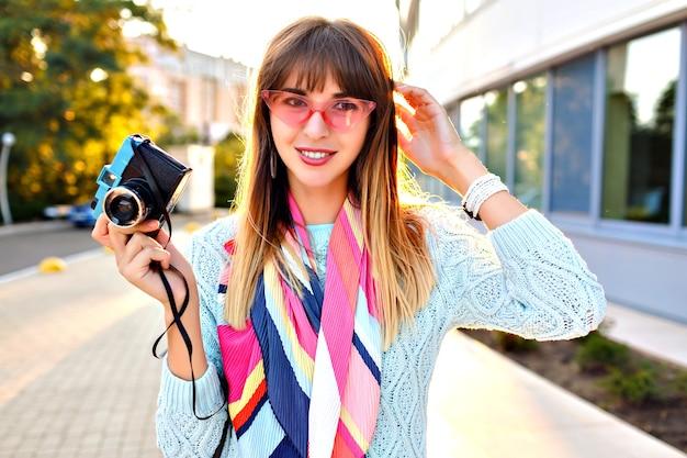 パステルセーターサングラスとスカーフを身に着けているレトロなビンテージフィルムカメラを保持している壮大な若いきれいな女性の屋外都市の肖像画を閉じます、日光。 無料写真