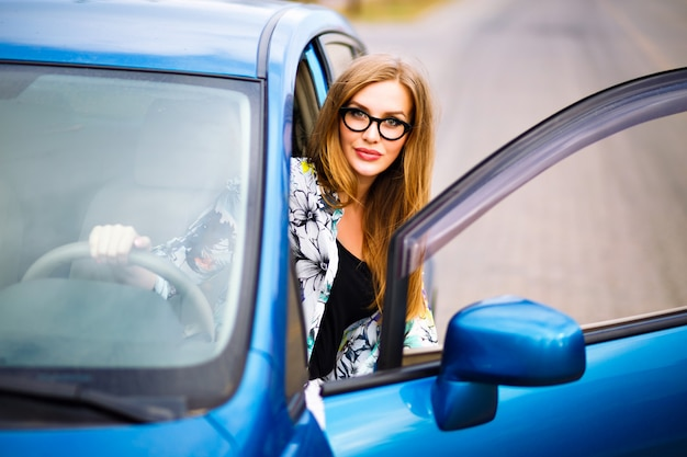 Close up outdoor lifestyle travel photo of young blonde hipster  woman driving car, glasses and bright clothes, big smile happy mood, enjoy her nice day, young businesswoman . Free Photo